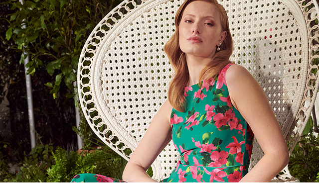 Model photographed in a garden wearing Hobbs Carly bougainvillea print dress.