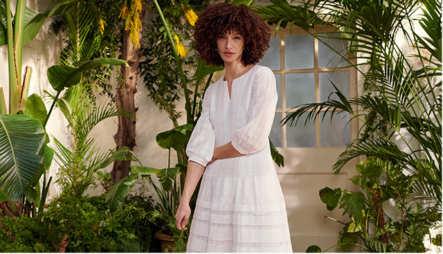 Model wearing a Hobbs cream summer dress in a conservatory.
