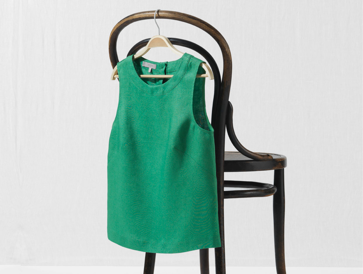 green top hanging from chair