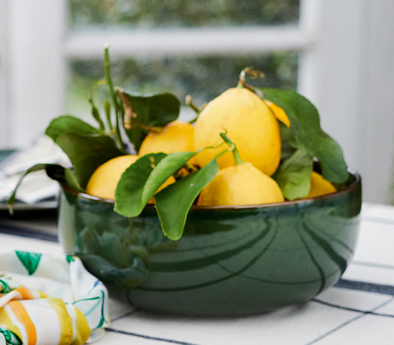 A jug of homemade lemonade, bowl of fresh lemons and a silk scarf sit atop a table.