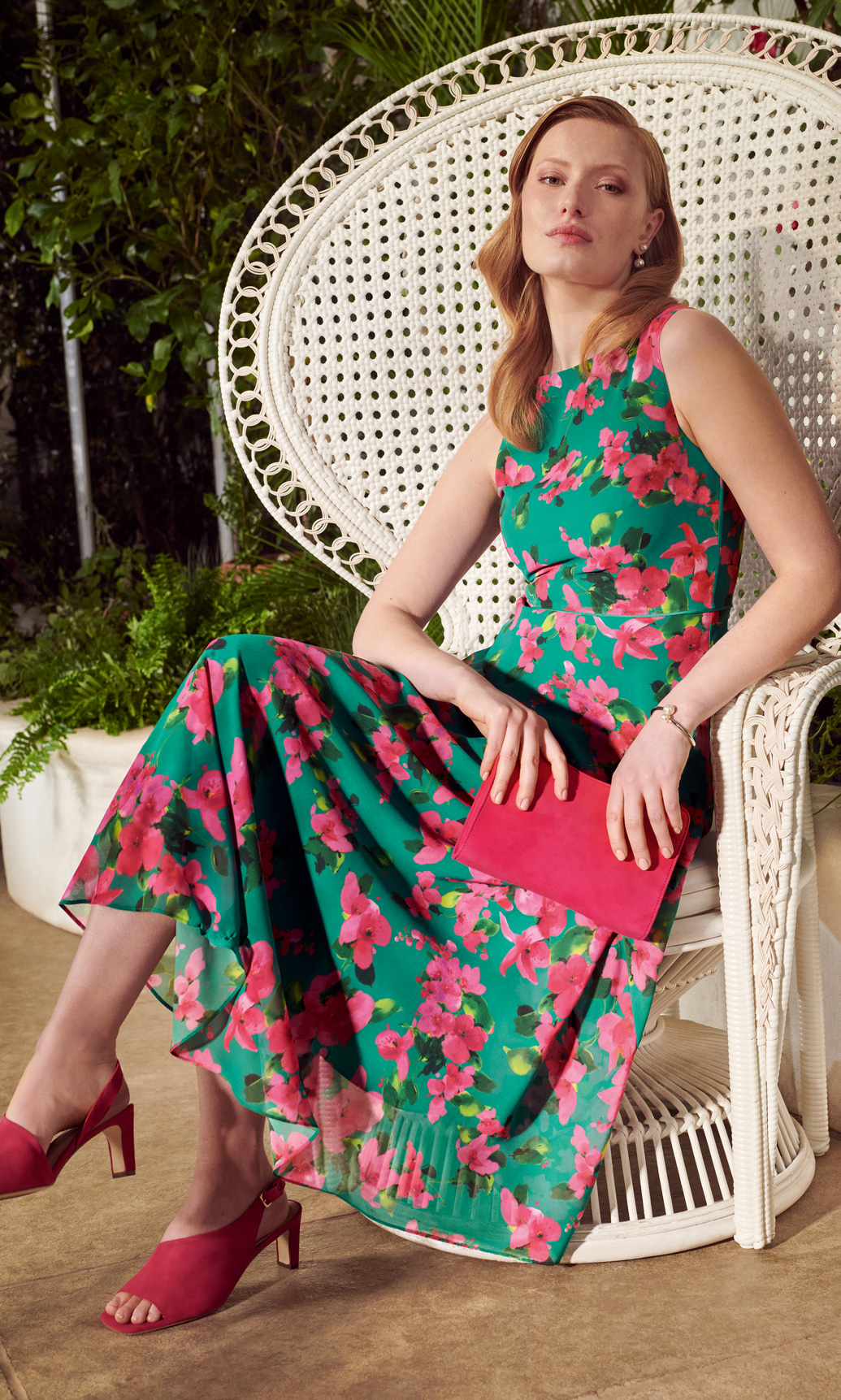 Model wearing a floral print midi dress and heels sits on a white peacock chair.