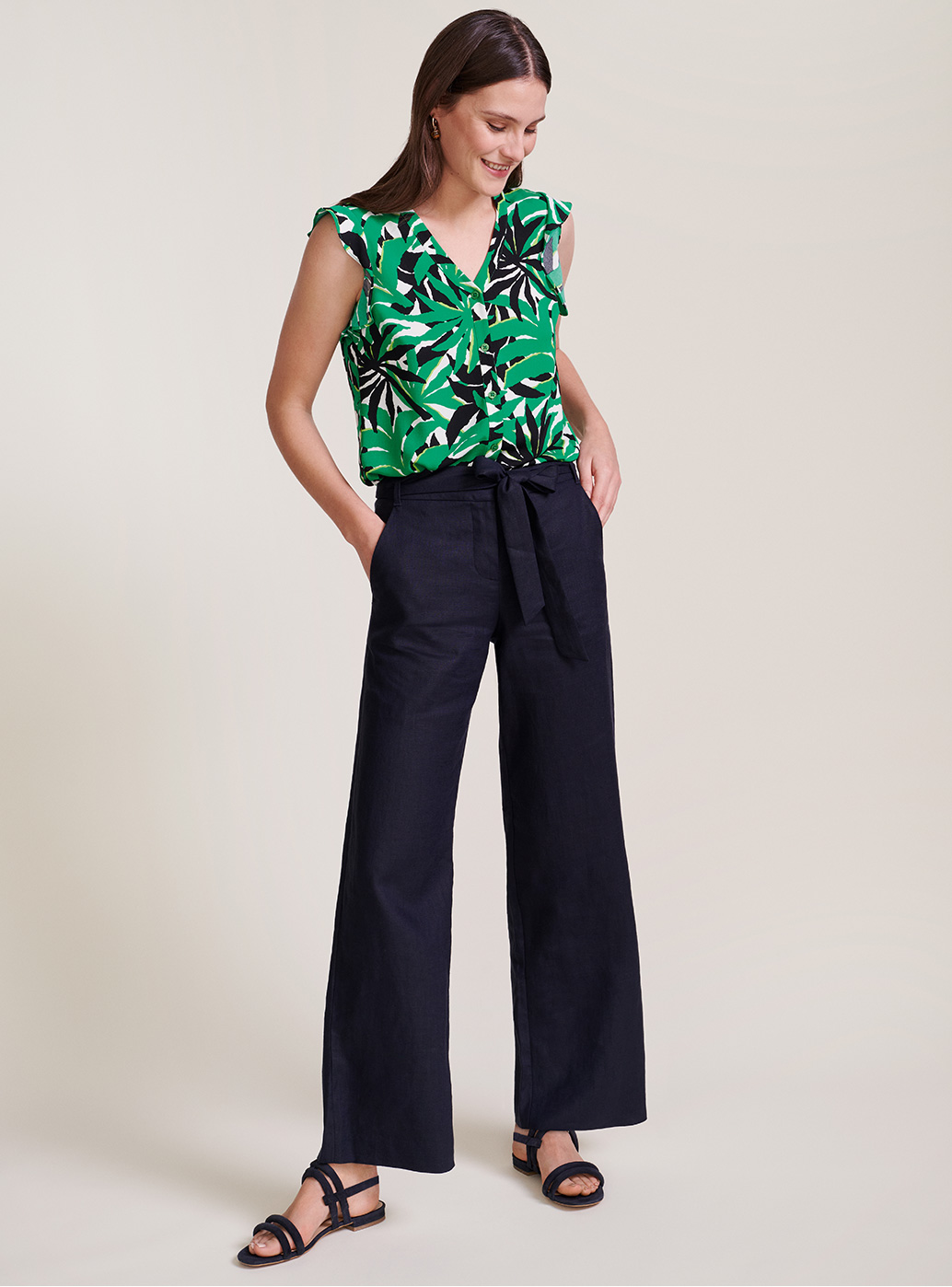 Model wears a jungle print blouse, tucked into wide leg linen trousers.