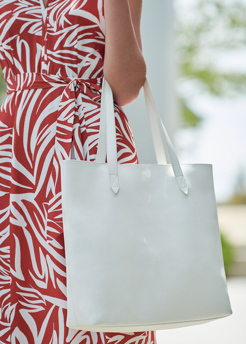 Detail shot of a white leather tote bag.