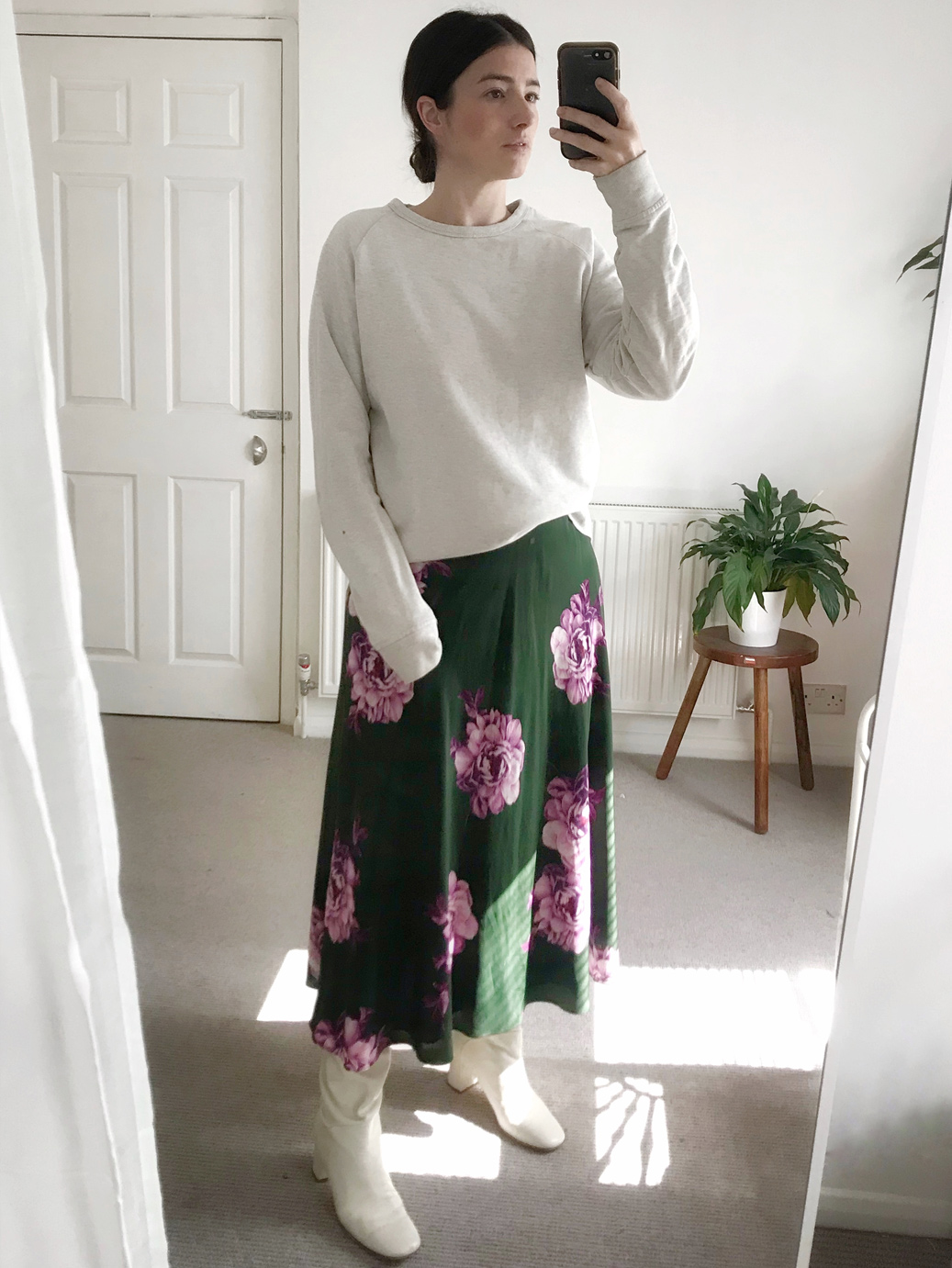 Maddy pictured wearing a floral dress and comfy white knit.