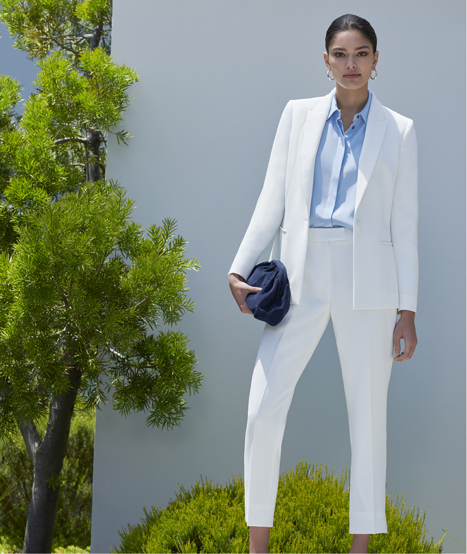 Women's trouser suit in white, worn with a light blue shirt and a navy blue clutch by Hobbs.