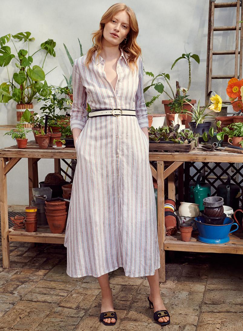 Model wearing a Hobbs striped linen shirt dress with black sandals in a garden. Alt text: Model wearing a Hobbs t-shirt with 'Hello Summer' slogan in a garden.