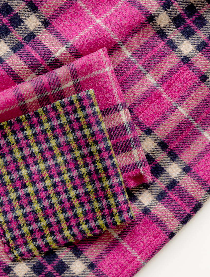Alt text: Close up shot of pink wool fabric with check patterns from Abraham Moon, a British woollen mill.