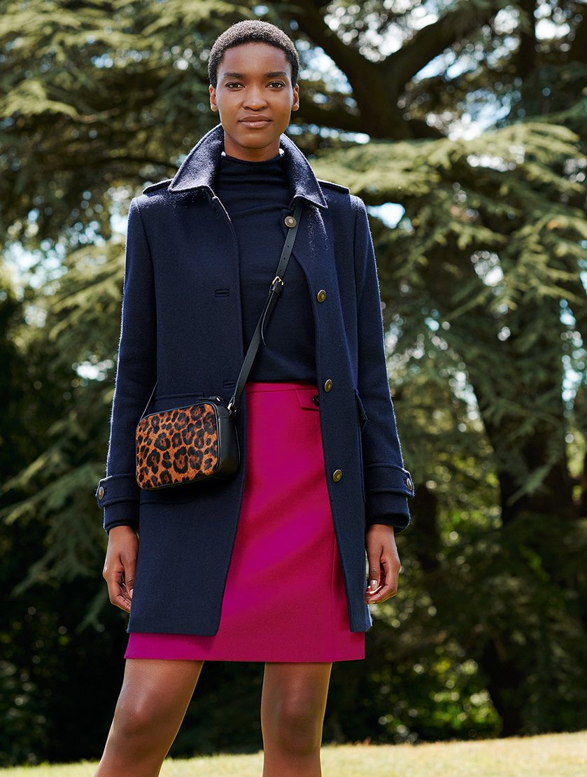 Alt text: Hobbs women's winter wool coat in dark navy blue layered over a dark roll neck jumper and a pink skirt with a leopard print leather crossbody bag.