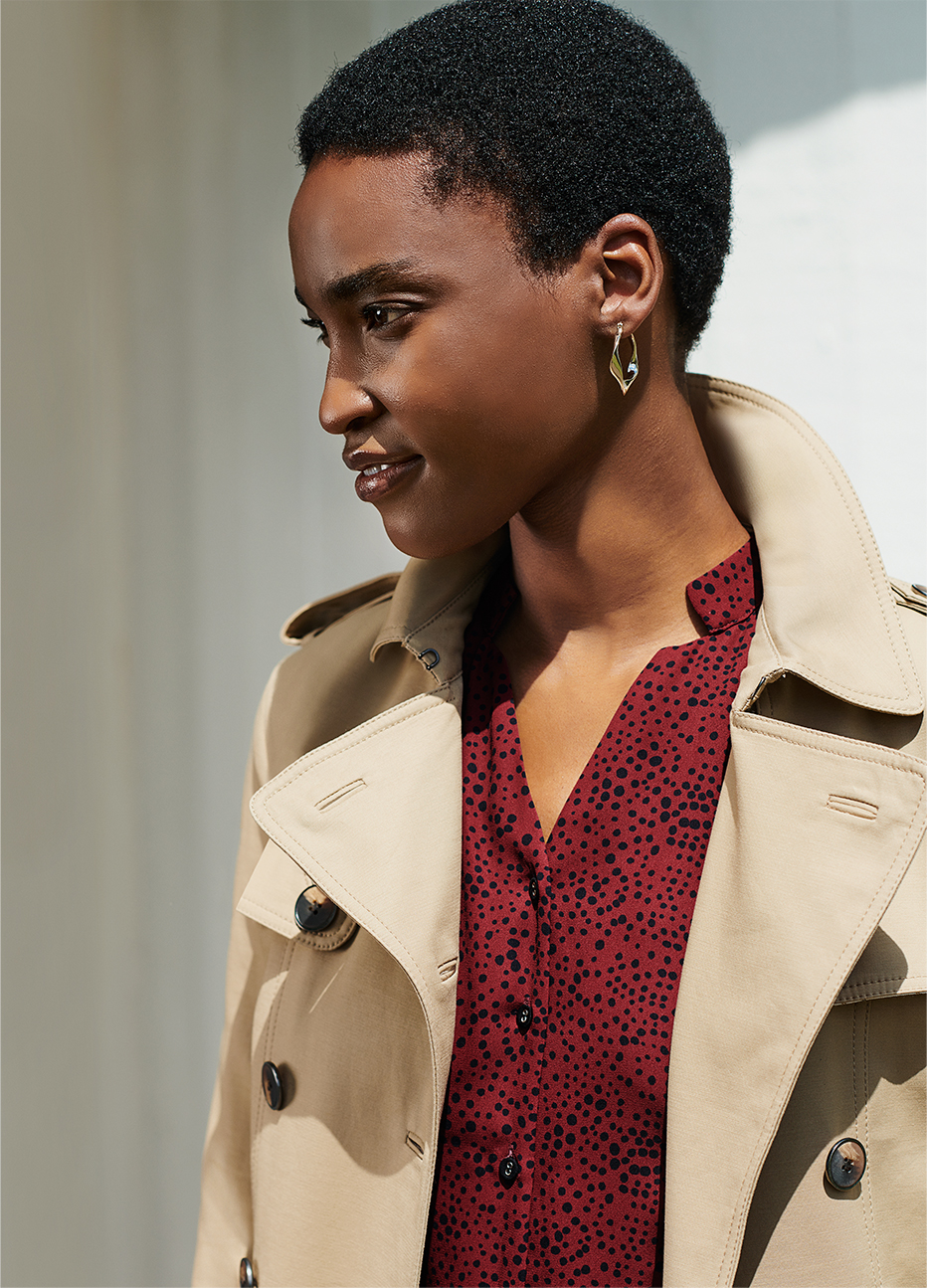 Hobbs model wearing a beige women's trench coat over a red shirt dress and hoop earrings.