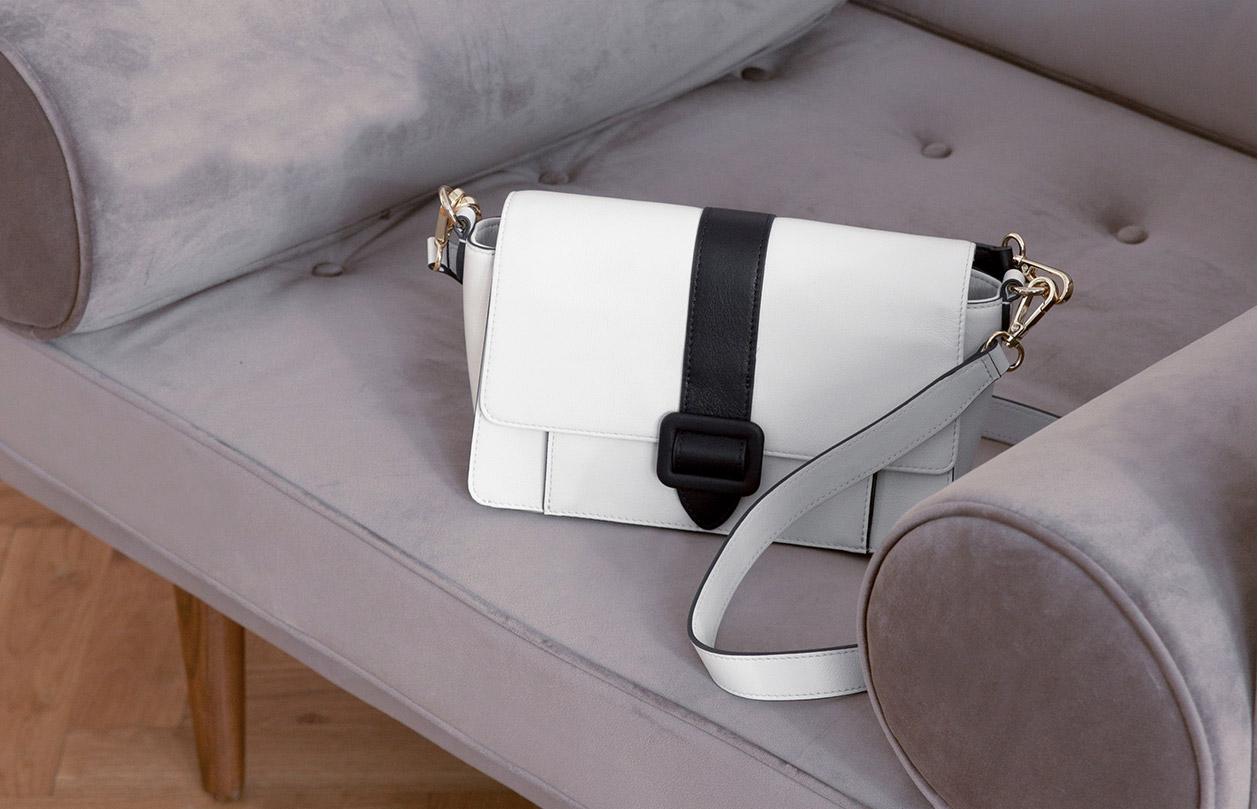 Hobbs satchel bag displayed on a grey sofa.