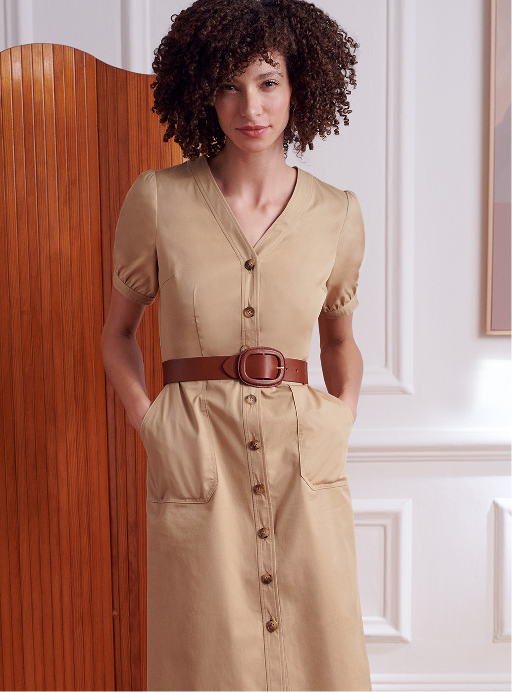 Model stands in front of a screen wearing a camel dress and tan leather belt.