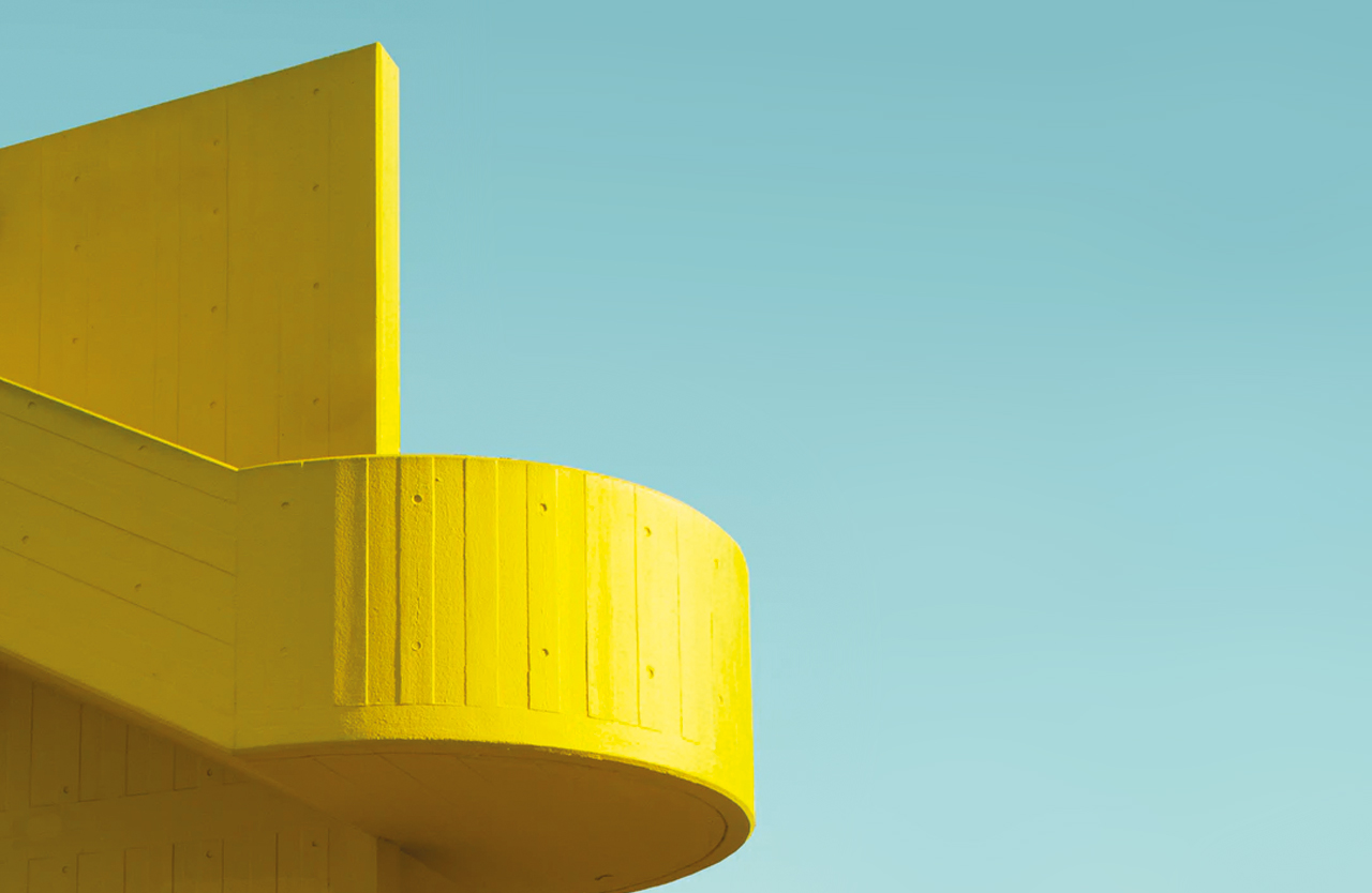 Yellow Modenist Designed Building Against A Clear Blue Sky