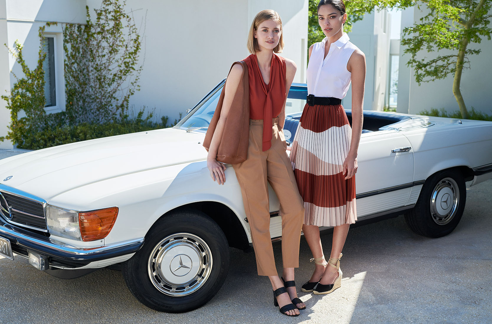 Two women pose in front of a white car, one wears a rust brown sleeveless blouse with tan tailored trousers with a black sandals and a brown tote bag, the other wears a white sleeveless blouse and a patterned brown, white, pink pleated midi skirt and black espadrilles.