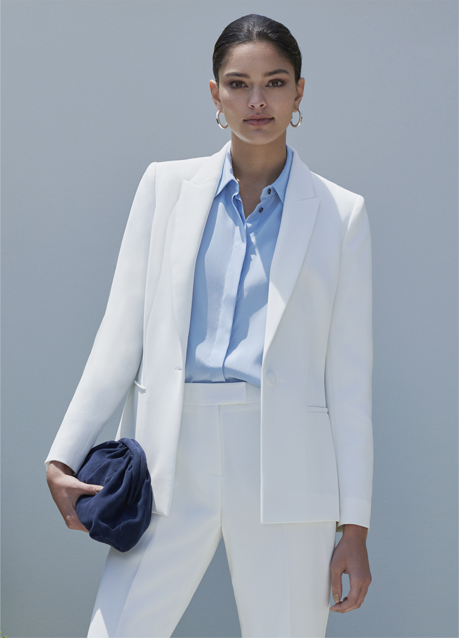 Women's trouser suit in white worn with a pale blue collared shirt and a navy blue suede clutch by Hobbs.