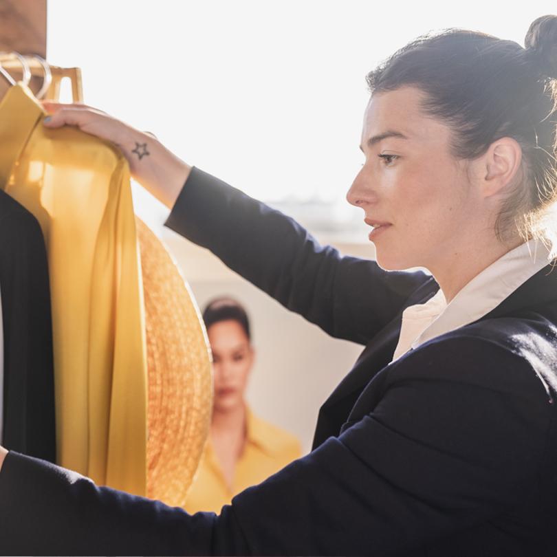 Hobbs Brand Stylist Maddy Moxham holds a yellow shirt