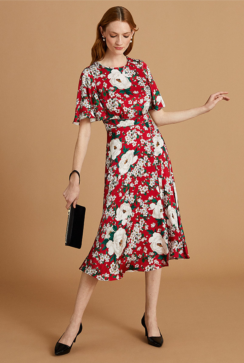 Model wears a red floral print midi dress with a black clutch bag and court shoes.