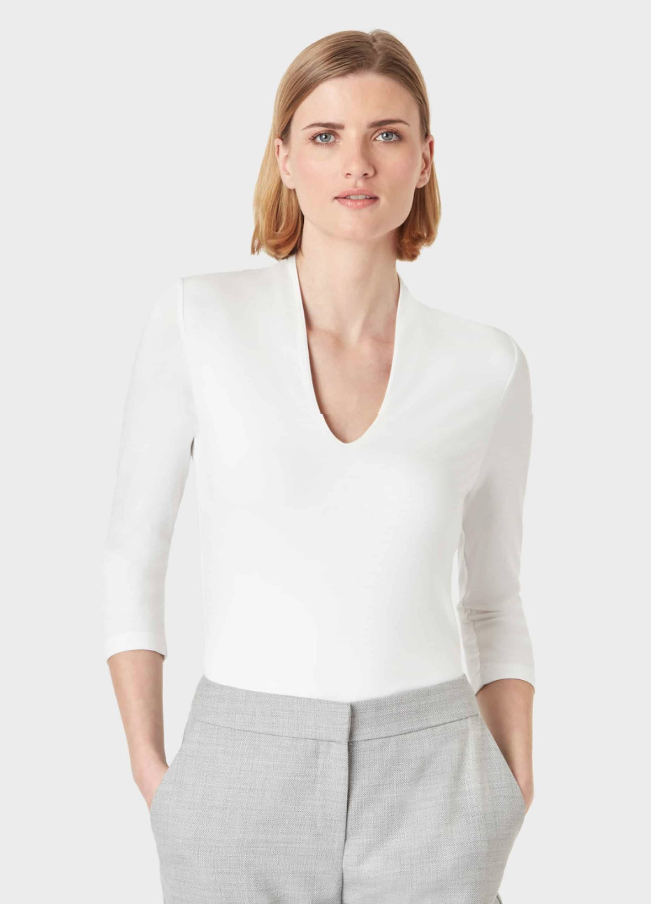 White v neck jersey top worn with grey tailored trousers by Hobbs.