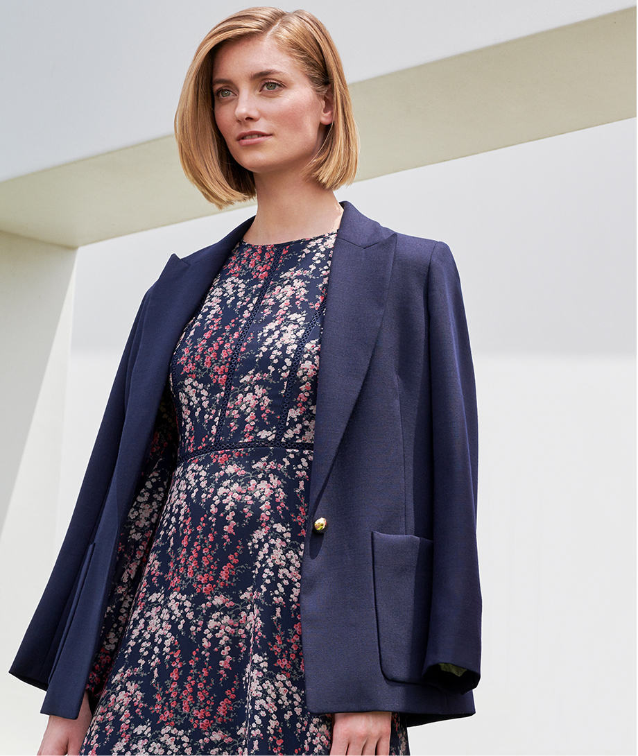 Navy blazer draped over a floral occasion dress by Hobbs.