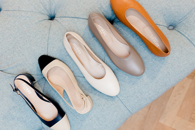 Five flat shoes laid out on a upholstered seat in a Hobbs store. From far left to far right: A slingback block heel flat with a black body and nude toe cap, a slingback block heel flat with a nude body and black toe cap, flat shoe in cream, flat shoe in light brown, flat shoe in orange.