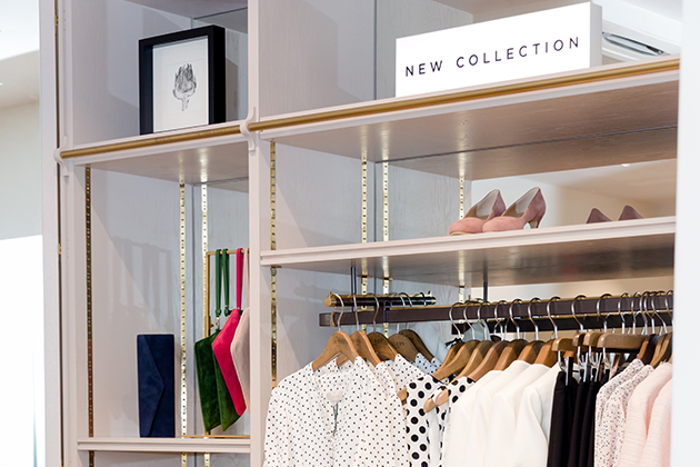 An image showing a section of a shelf in a Hobbs store. The shelf is decorated with a piece of framed artwork, a new collection sign, wrislets in blue, green, pink and white, court shoes in blush pink, and the upper half of a few hung up garments which include a dotted shirt in black and white, a polka dot top in black and white placed next to other designs in white, black and pink.