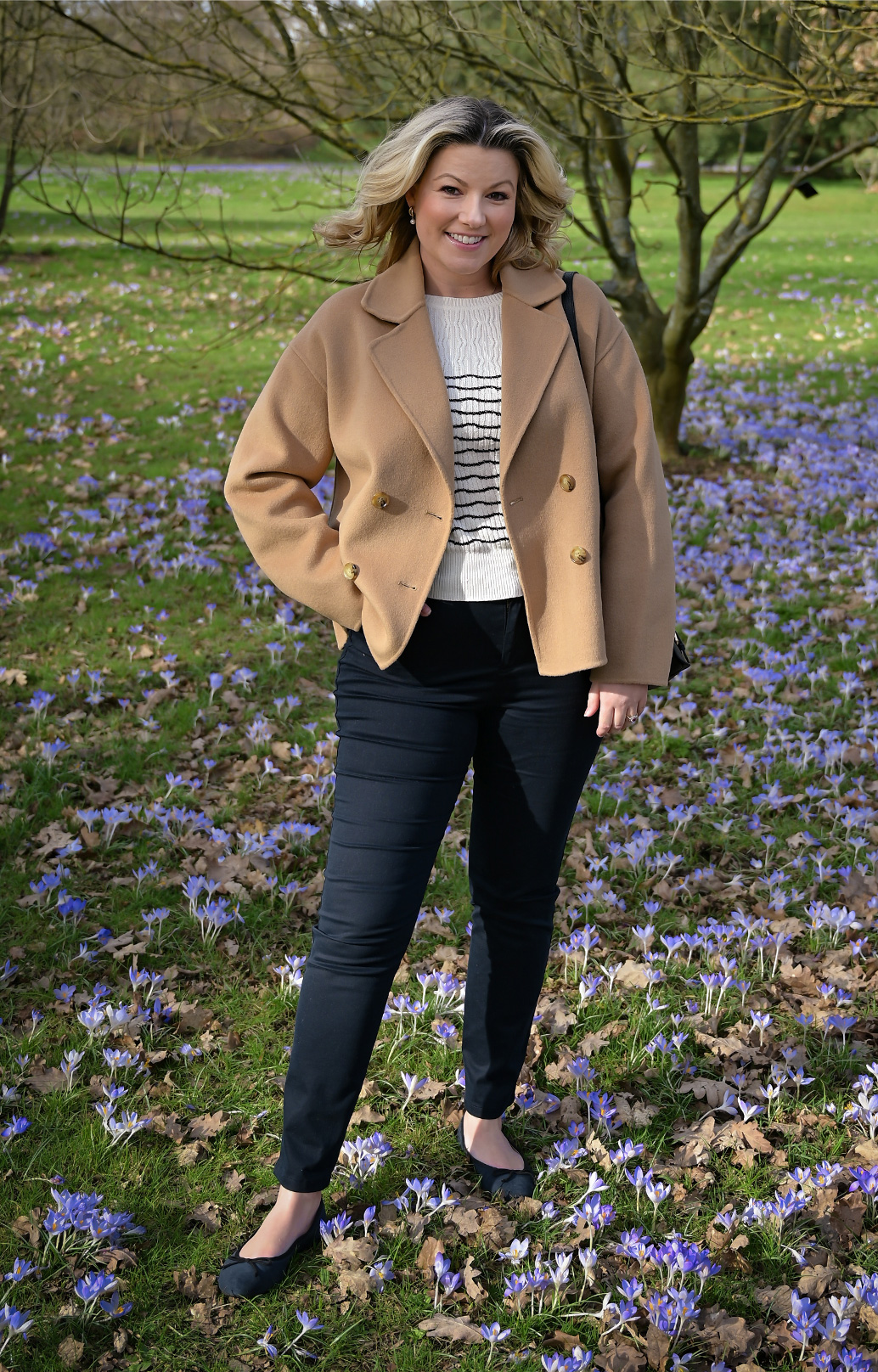 Singer Natalie Rushdie photographed on a walk wearing Hobbs Rosanna camel jacket, Daniella jumper and Gia black jeans.