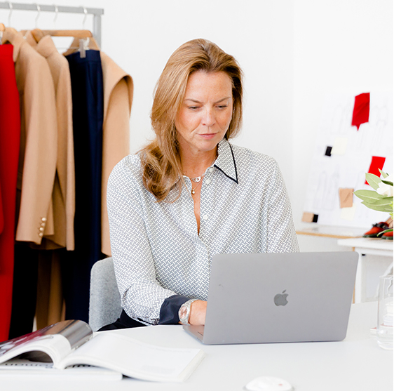 Hobbs' Product Director, Sally Ambrose, photographed wearing a silk shirt while working on her laptop.