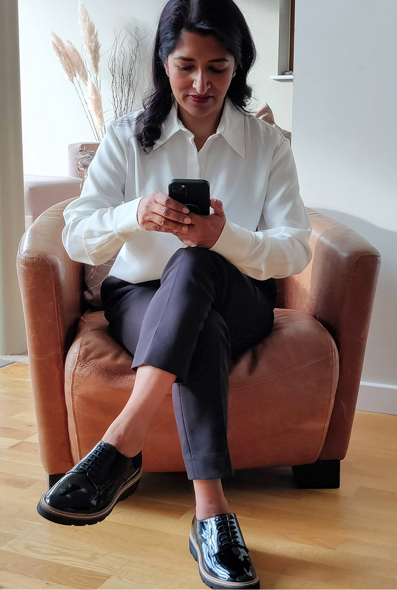 Photographed at home on her phone, fashion blogger Monika Mandal wears Hobbs Eva silk shirt, petite Quin navy trousers and Bloomsbury black patent lace-up shoes.
