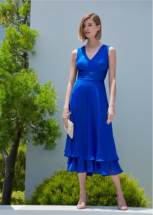 A woman poses in a cobalt sleeveless midi dress with nude court shoes and clutch bags