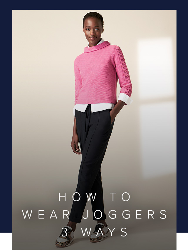 Model photographed wearing a pink knitted jumper with navy joggers and trainers.