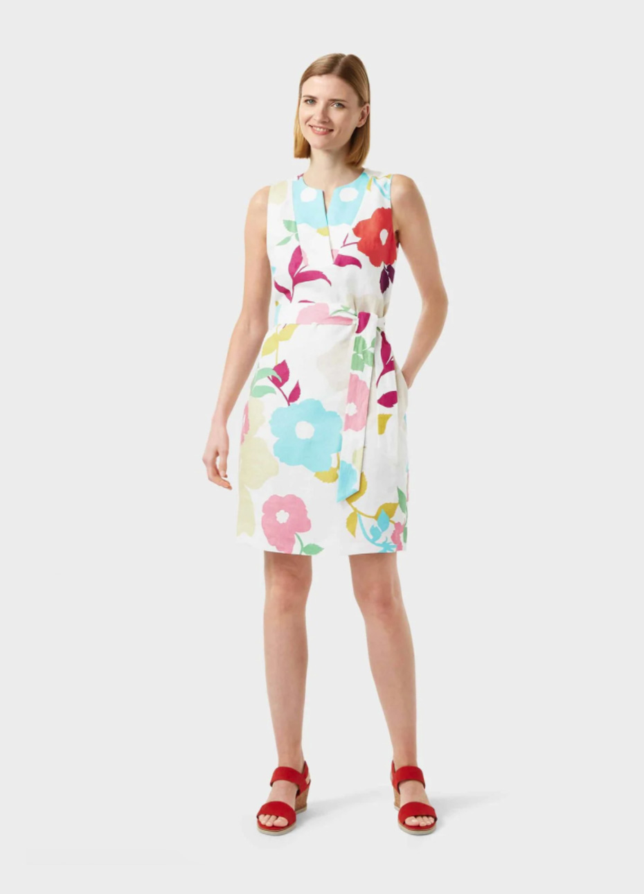 White shift dress with a multi-coloured floral pattern with a waist-tie paired with red block heel sandals by Hobbs.