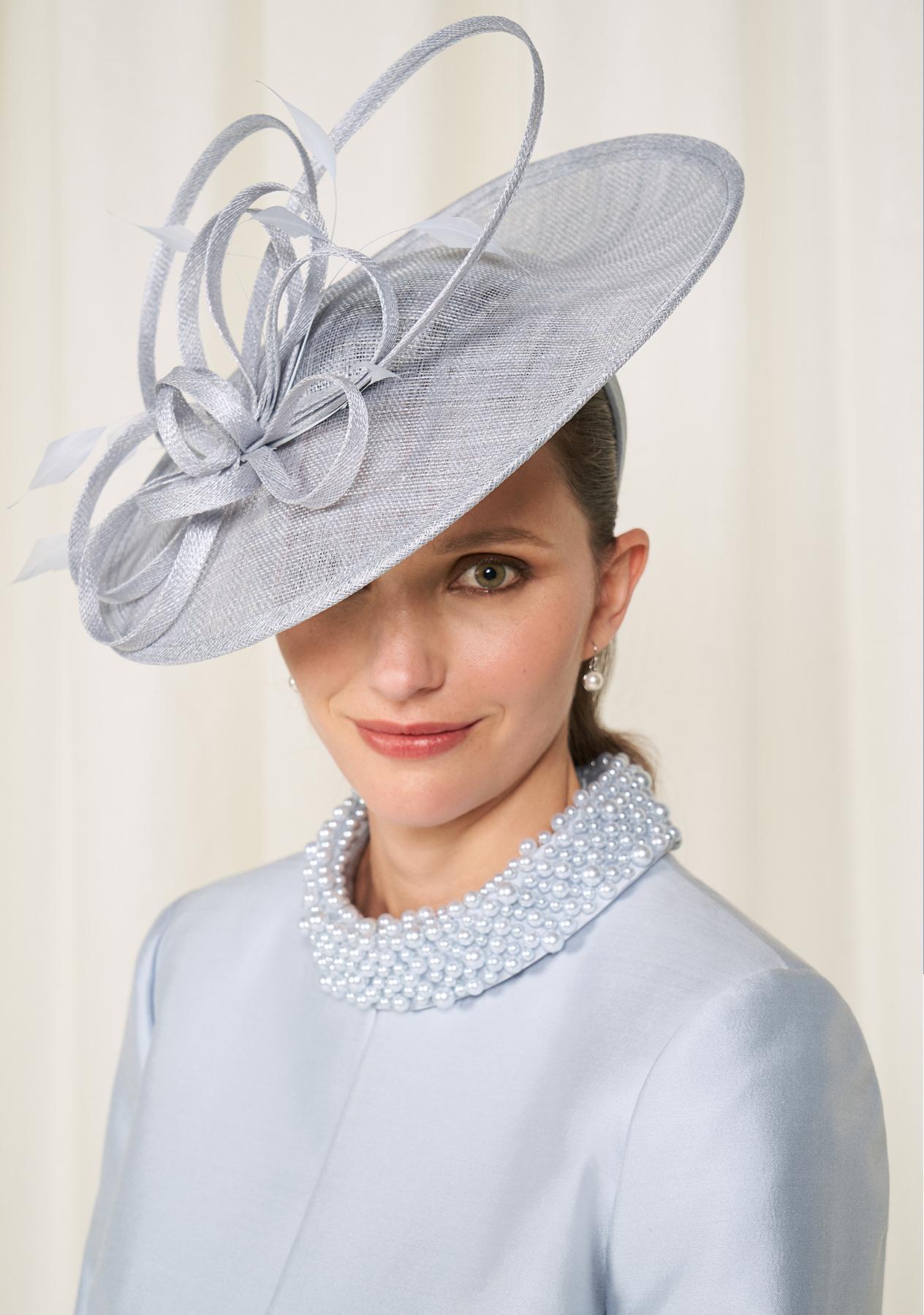 Model wears an embellished dress and fascinator.