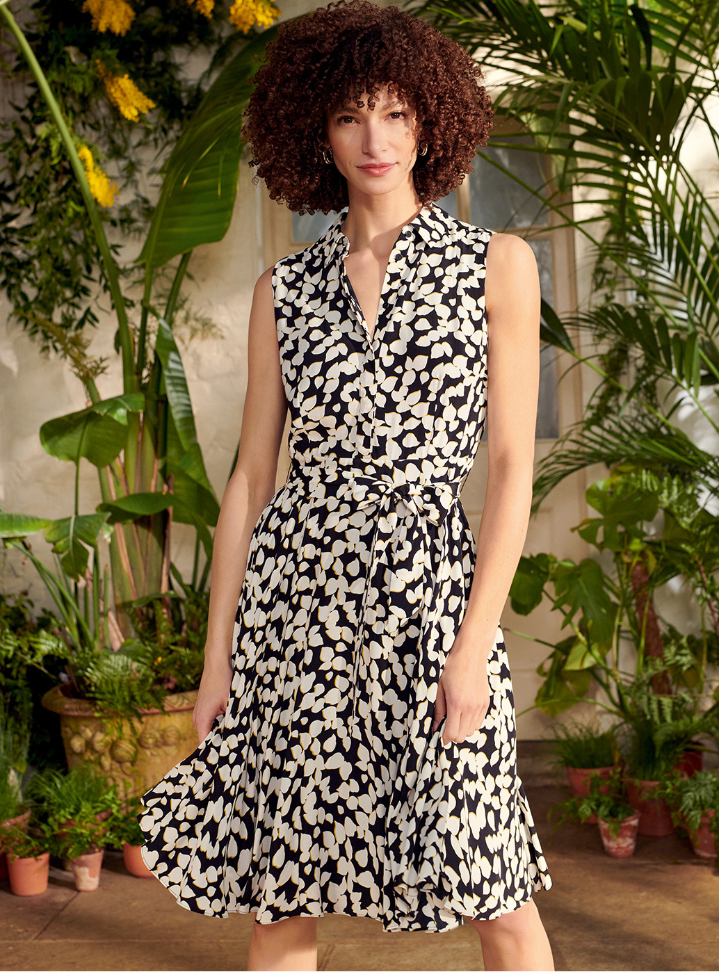 Model in a sleeveless shirt dress stands in a conservatory surrounded by greenery.