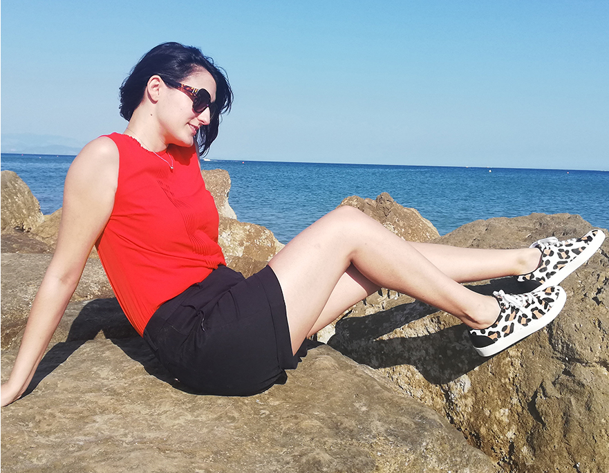 Marta Bonfaci, Senior Ecommerce Assistant at Hobbs poses on the rocks by the seaside wearing a red top, navy shorts, leopard print trainers and sunglasses.