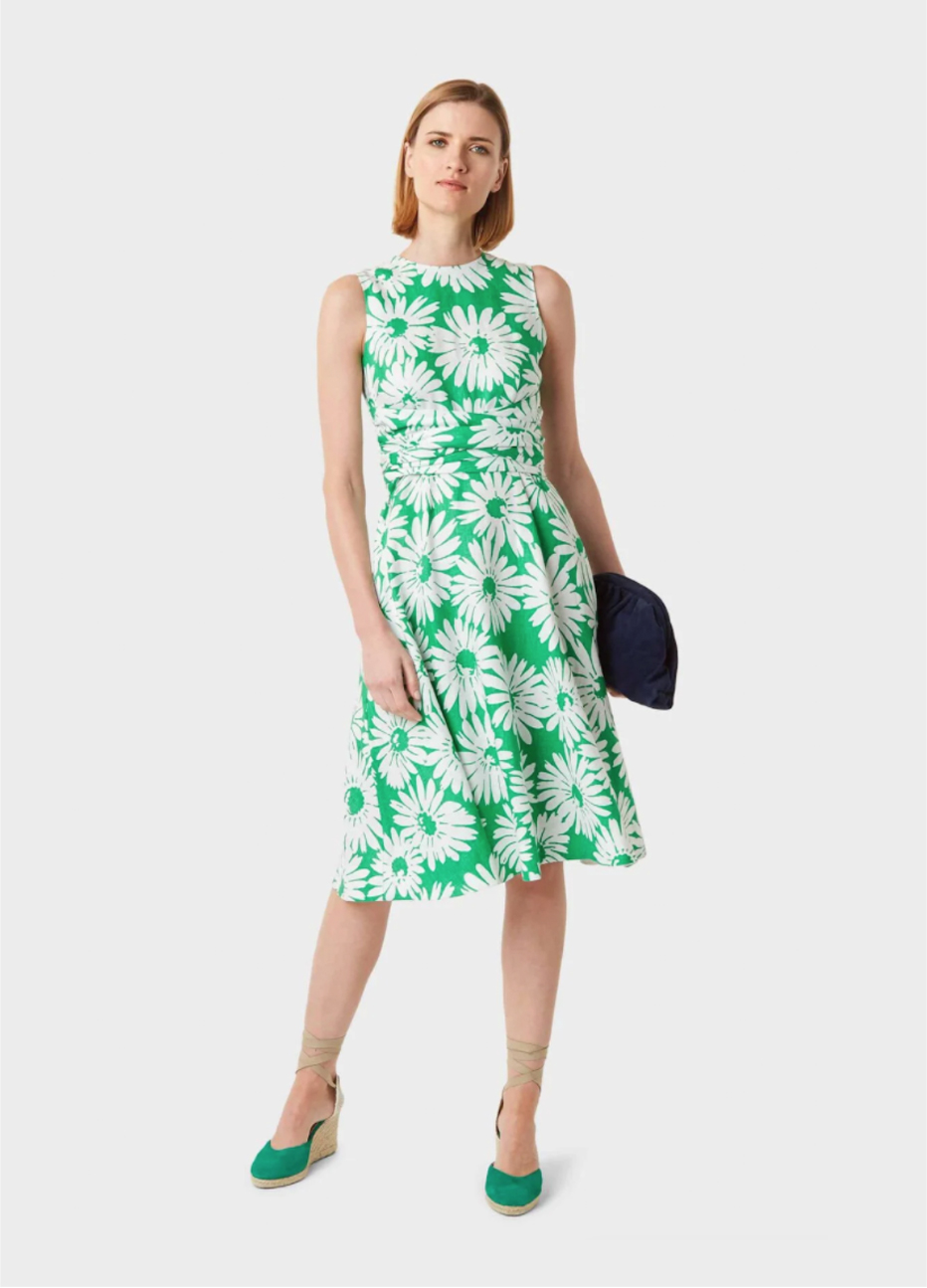 Green fit and flare shift dress with a floral pattern paired with wedge espadrilles in green and a black clutch bag, by Hobbs.