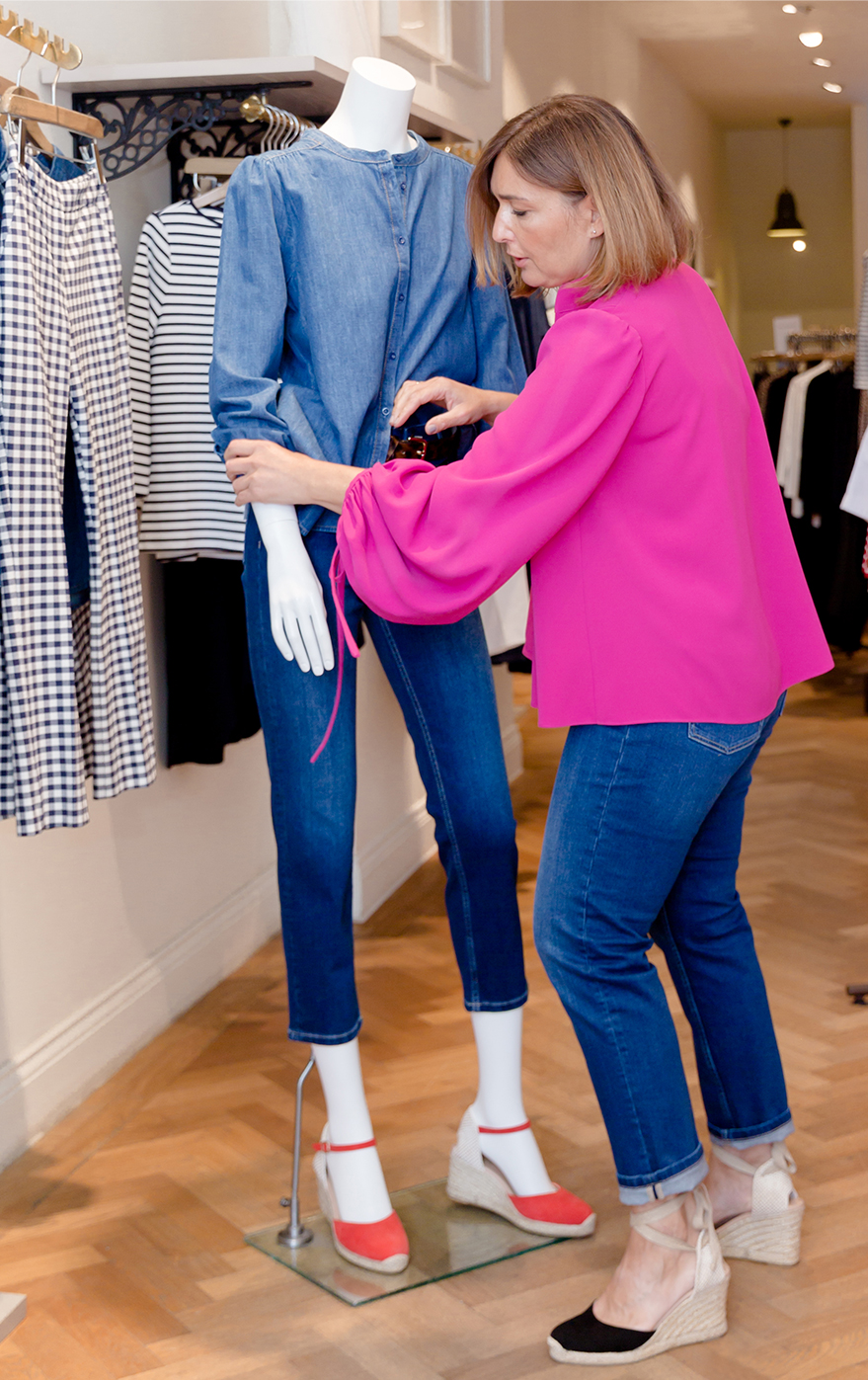 Hobbs UK & International Visual Specialist, Selena Trkuljia, photographed wearing a pink blouse while perfecting details of a mannequin in-store.