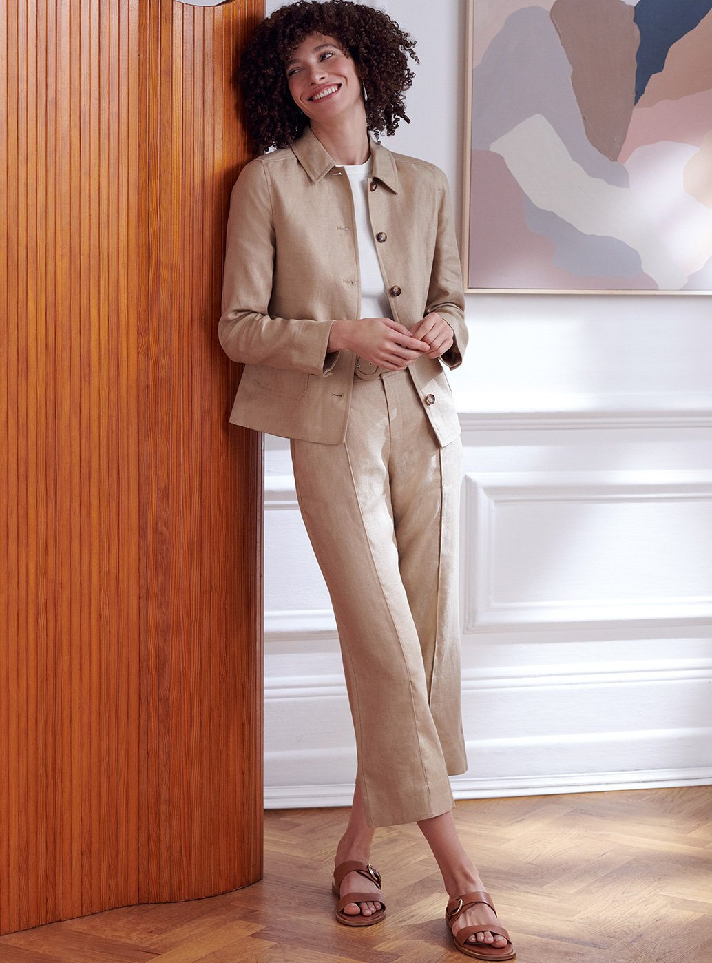 Model wears a beige linen suit and brown leather sandals.