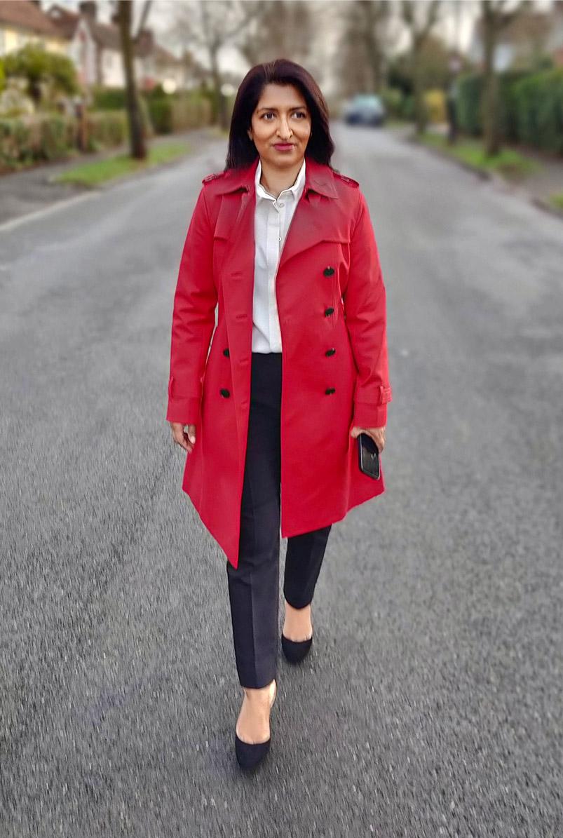 Photographed walking along her street, fashion blogger Monika Mandal wears Hobbs petite red Saskia trench.