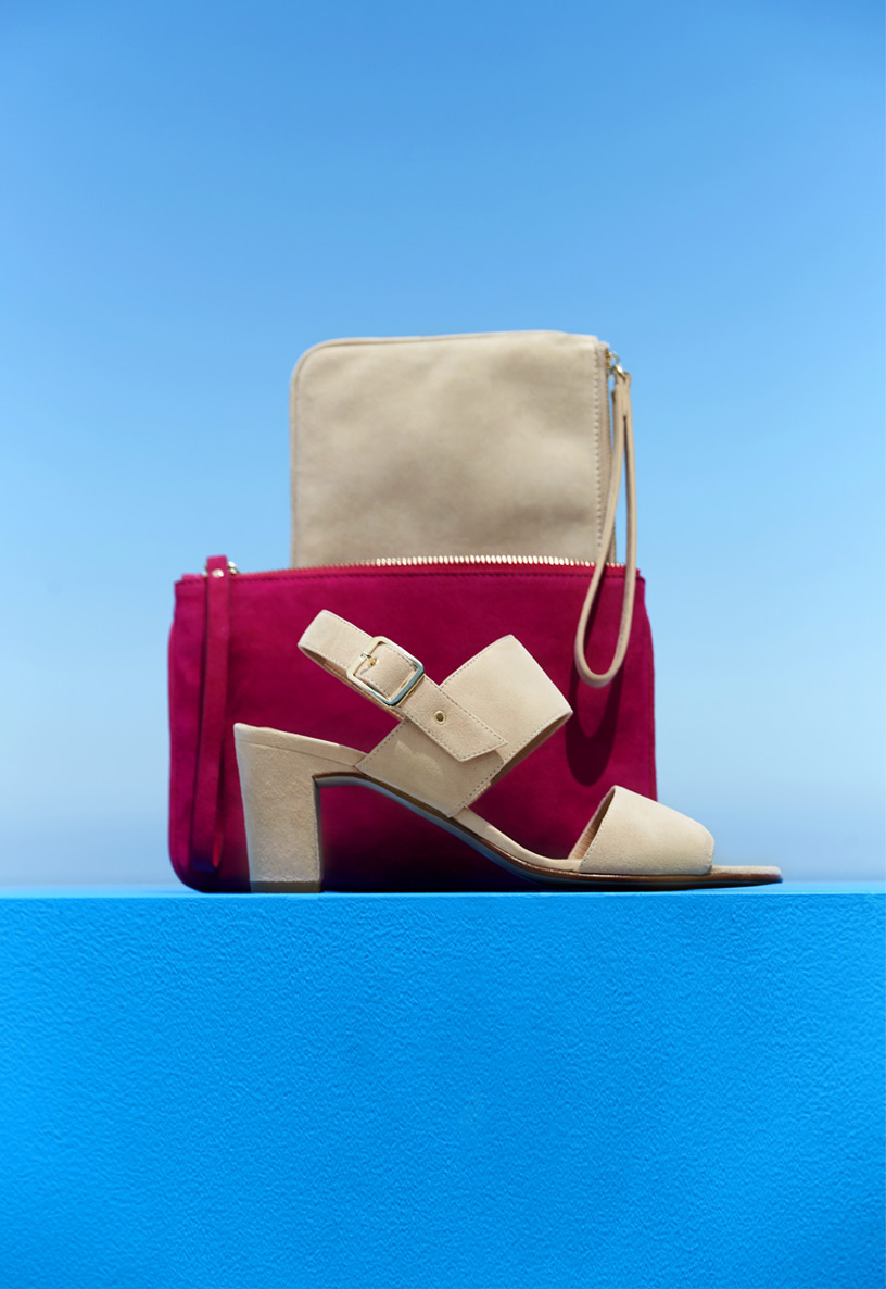 Architectural grouping of a cream and bright pink suede clutch bag with matching cream suede heeled sandals.
