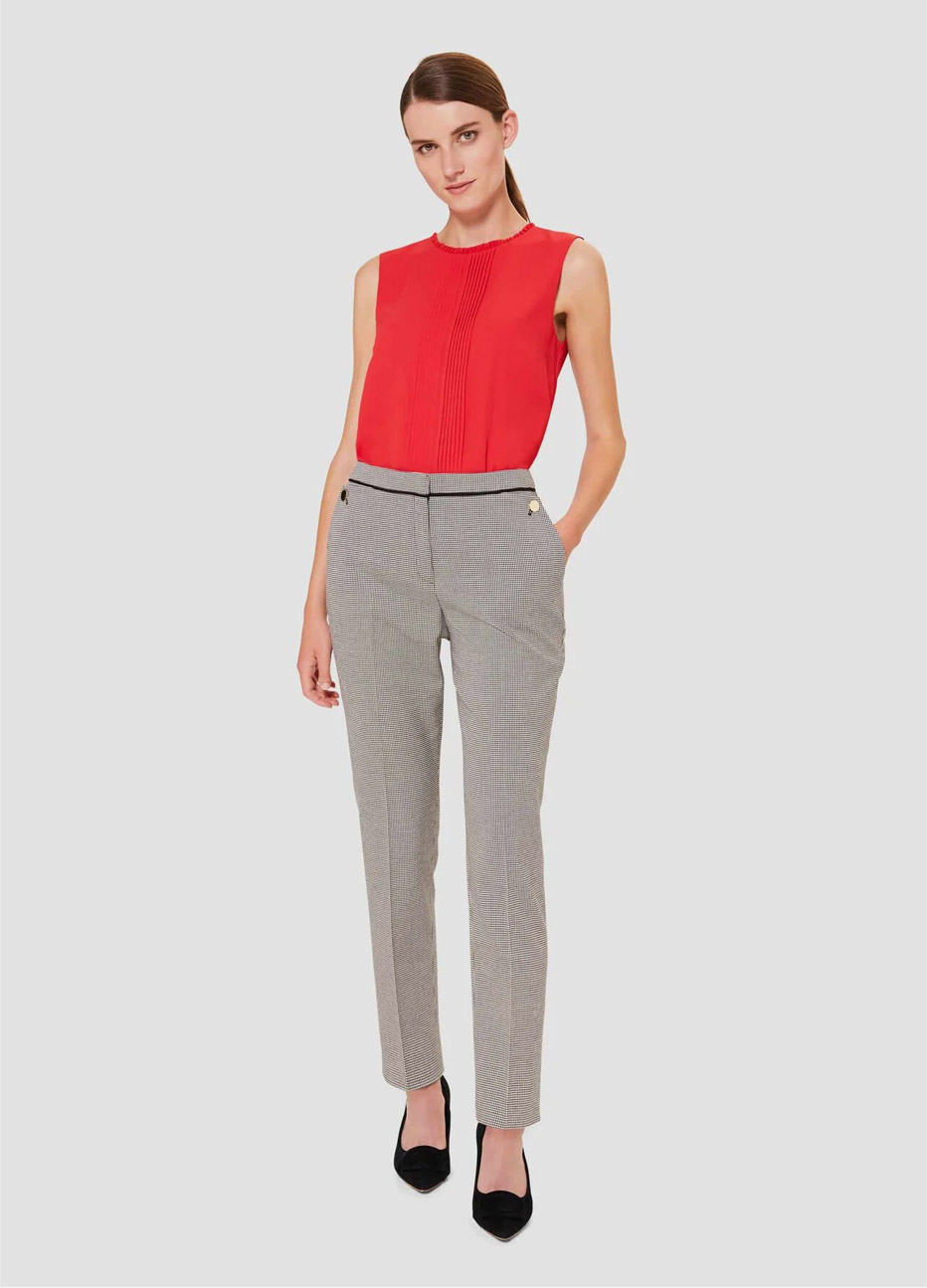 Red top with slim tailored trousers for women worn with black court shoes by Hobbs.