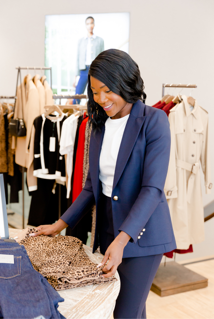 Store Manager, Tayo Olode-Okuta, photographed arranging a leopard print jumper on a table in a Hobbs store.