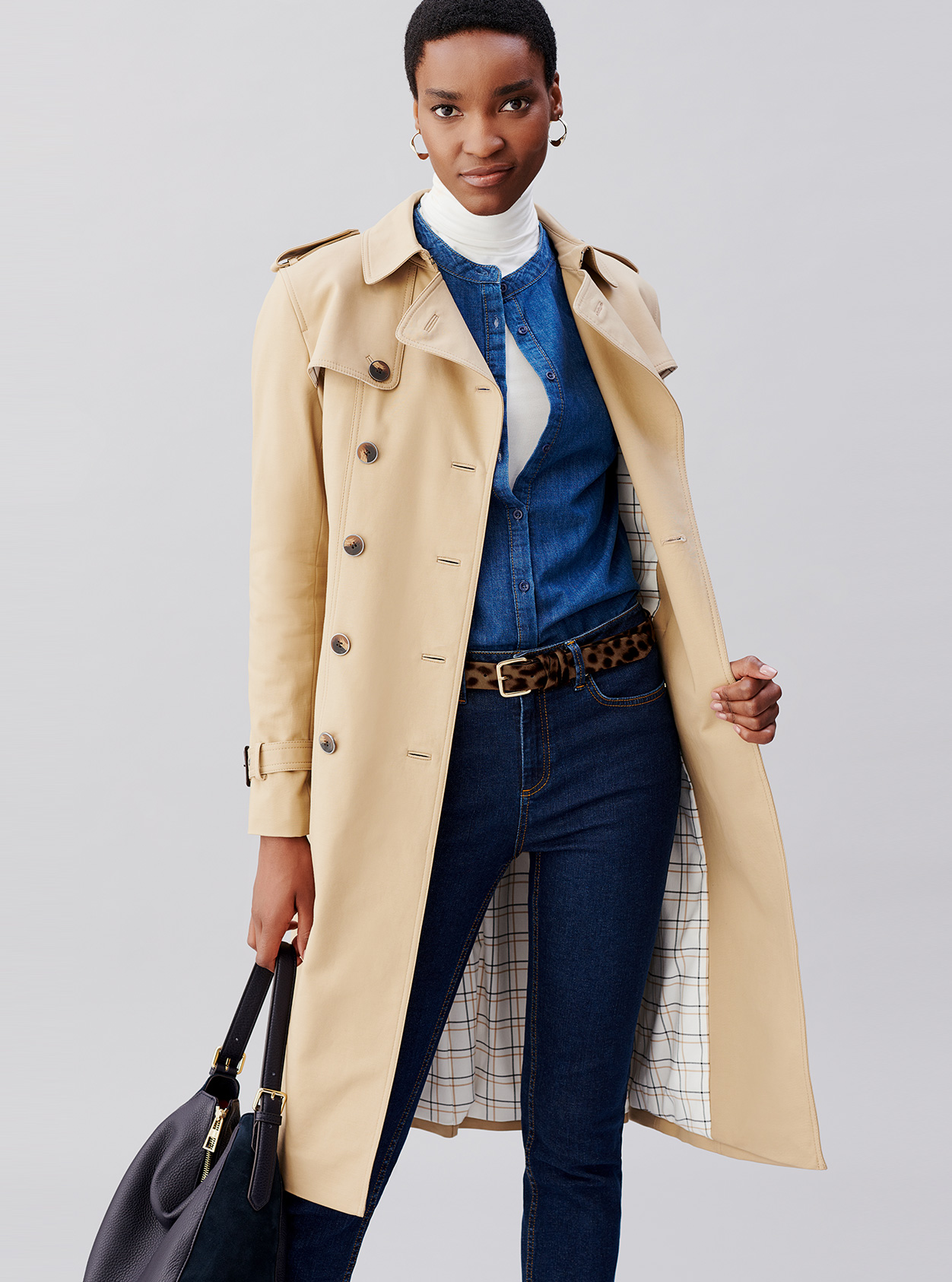 Hobbs beige trench coat for women layered over a denim shirt, white turtleneck top, blue denim jeans, leopard print belt and a black leather bag.