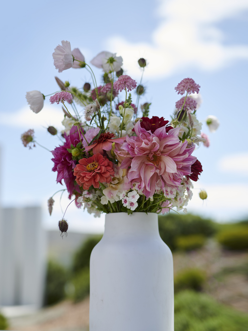 A bouquet of pink, red and white spring flowers in a white ceramic vase.