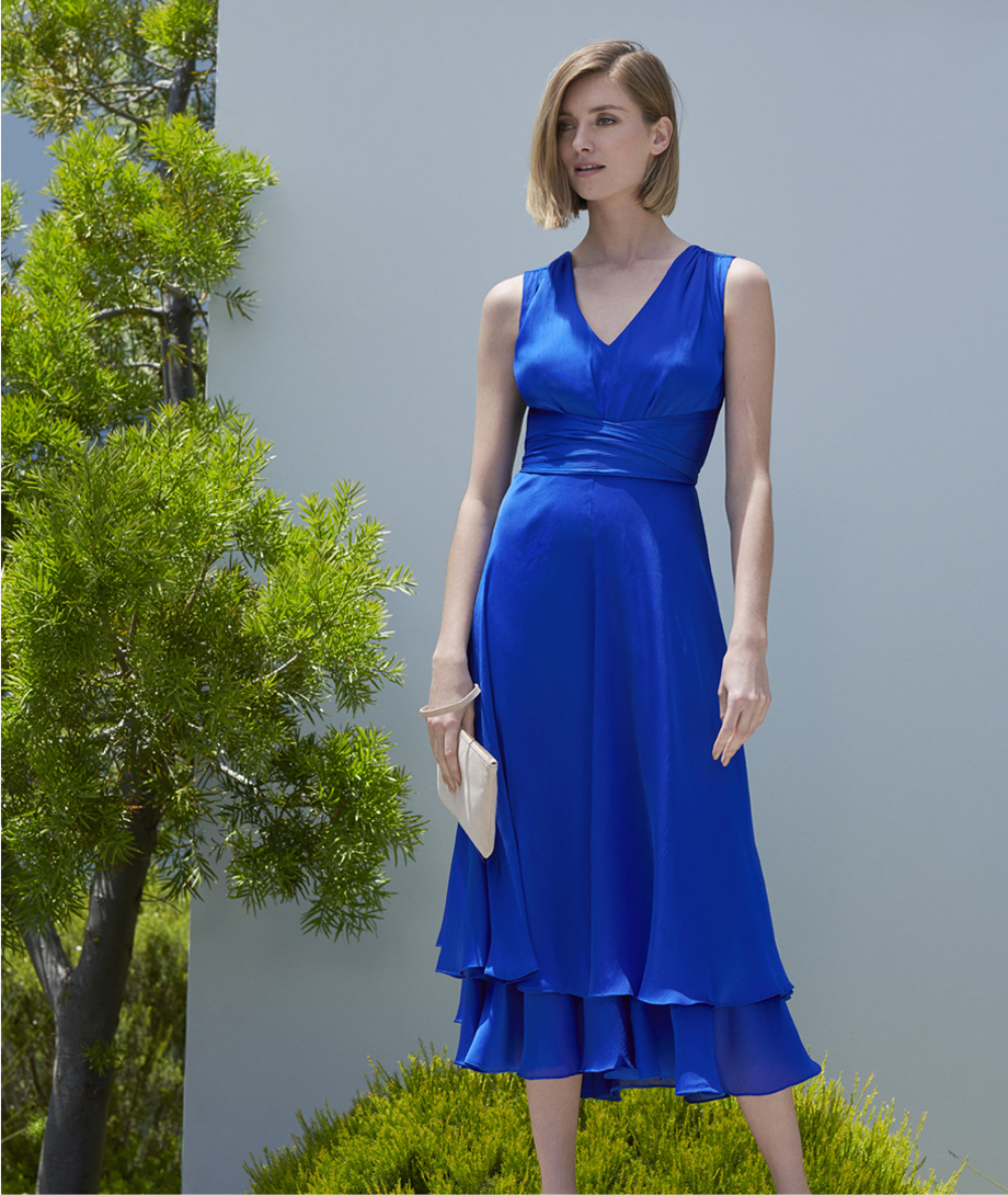 Midi length sleeveless dress in blue with a white clutch by Hobbs.