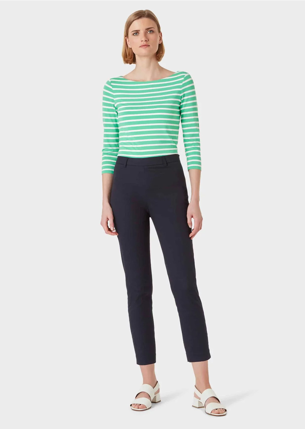 Blonde woman poses in a studio wearing navy blue slim fit trousers and a green and white striped top.