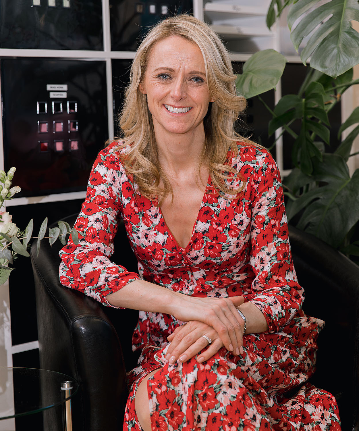 Kate Stephens, Ceo of Smart Works Charity wearing a floral red dress seated at an event