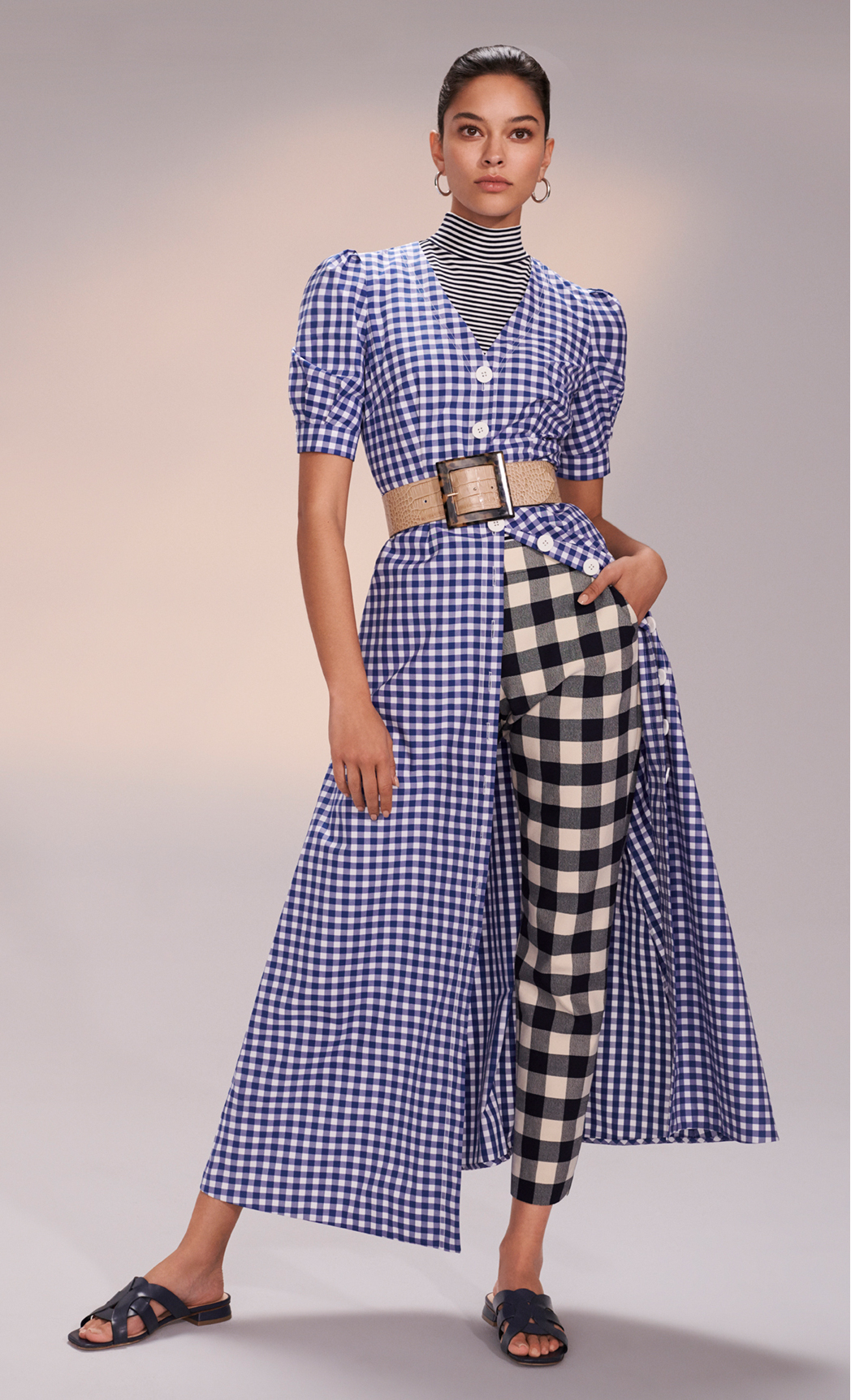 Model poses in blue gingham midi dress styled with trousers and navy sandals