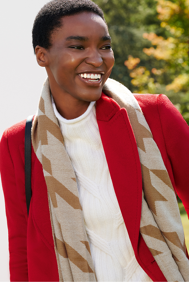 Close-up image of model wearing a Hobbs red coat, a cream jumper and a houndstooth scarf.