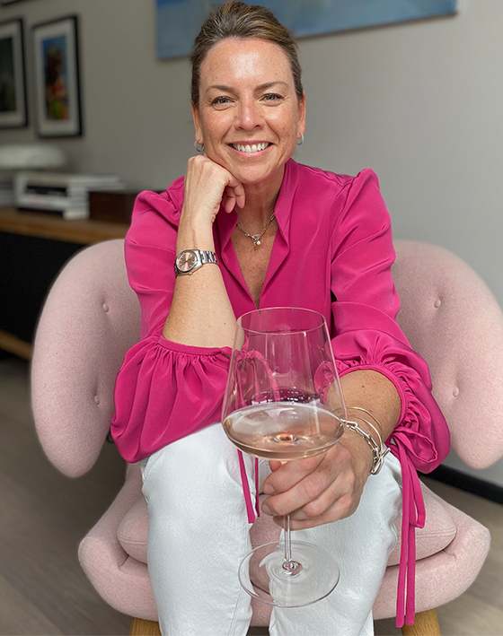 Sally Ambrose, Hobbs Product Director pictured at home in a pink blouse and white jeans