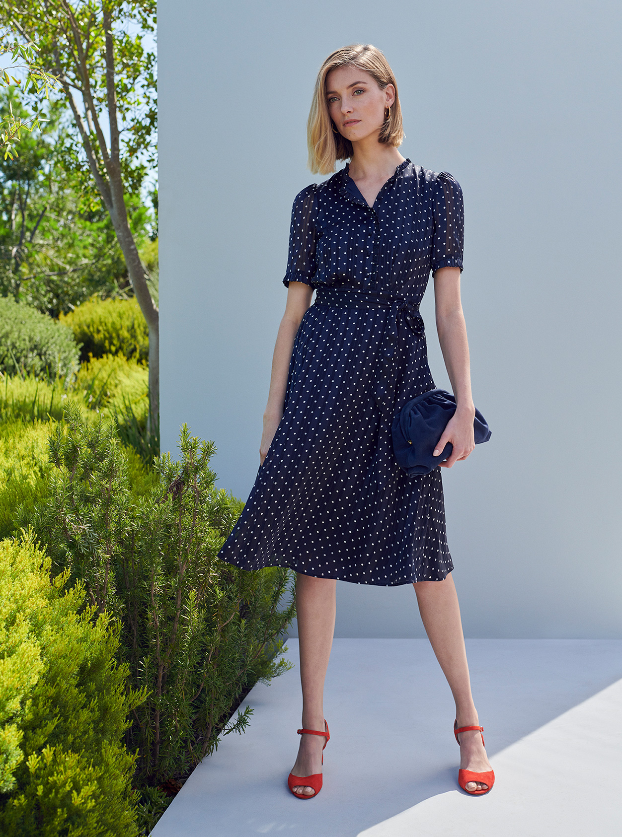 A woman poses in a navy blue and white spotty silk shirt dress with red heeled sandals.
