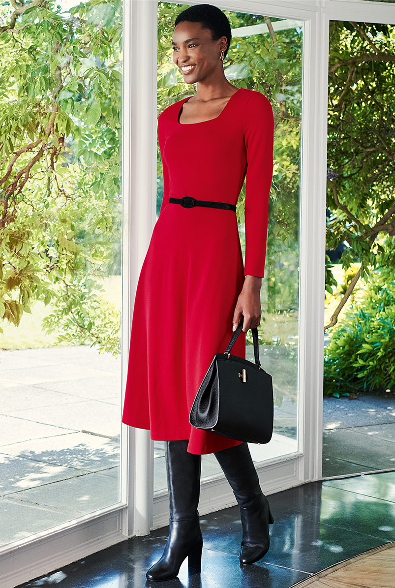 Full length image of model wearing a Hobbs red dress with long black boots.